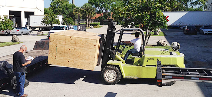 logistic operations - unloading crate from a low boy trailer